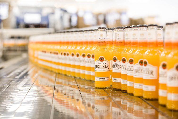 Die kleinen Bacardi Breezer Flaschen werden auf Fliessbänder durch das Werk gefahren. | © Eric Shambroom Photography